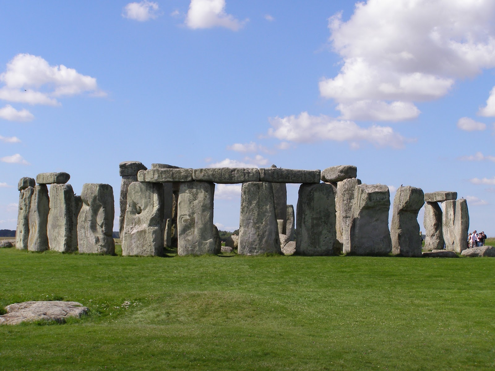 stonehenge natural wonder of the world. Rock formation on a green lawn during a sunny day, some tourists near the right end of the frame.