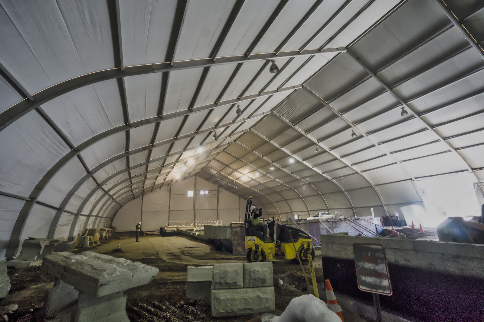 interior of construction or infrastructure project temporary fabric building high ceiling aluminum frame with worker and cement and other construction materials inside