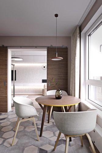 Cozinha contemporânea com piso cimentício em formato hexagonal, mesa redonda de madeira com cadeiras brancas, luminária pendente e porta de correr de madeira