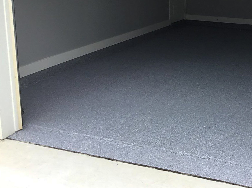 A garage floor with a blue colored coating that goes right outside the garage door.