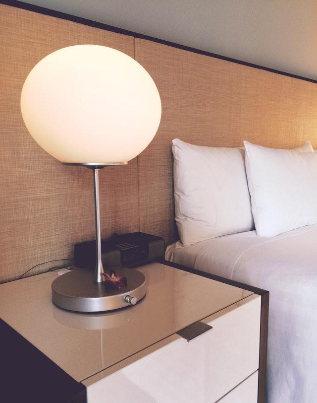 a big, bedside lamp on a white bed night table