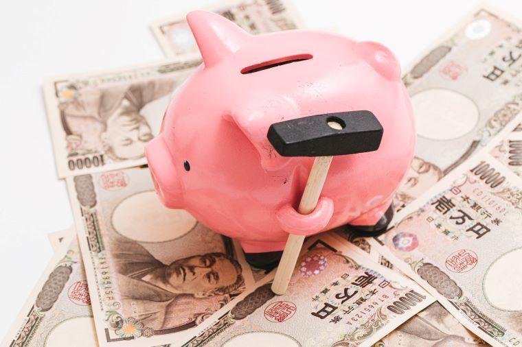 お札の上に置かれている豚の貯金箱