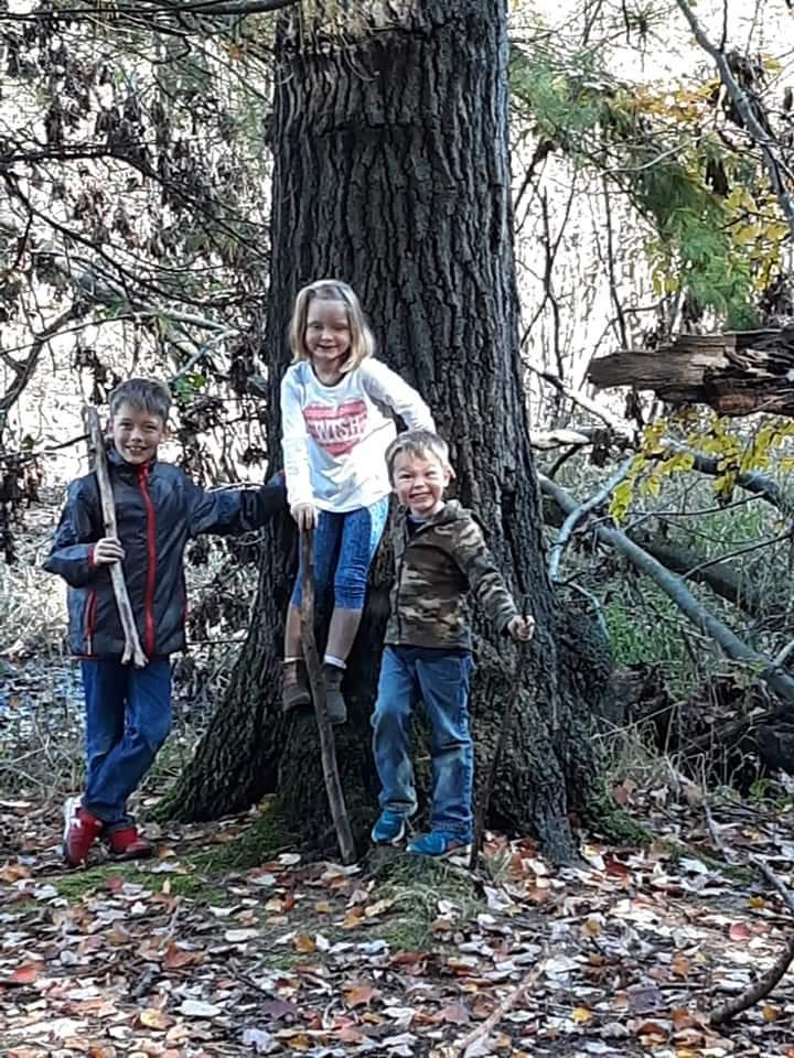 A group of children standing next to a tree  Description automatically generated with medium confidence