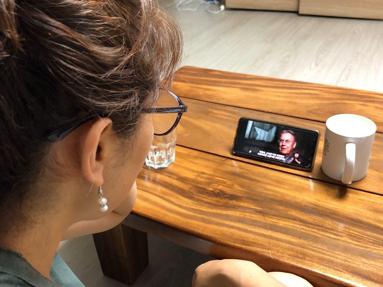 사진1. 서울인권영화제의 자원활동가 망나의 집. 망나의 가족이 테이블 위 핸드폰으로 <컨베이어벨트 위의 건강>을 보고 있다.