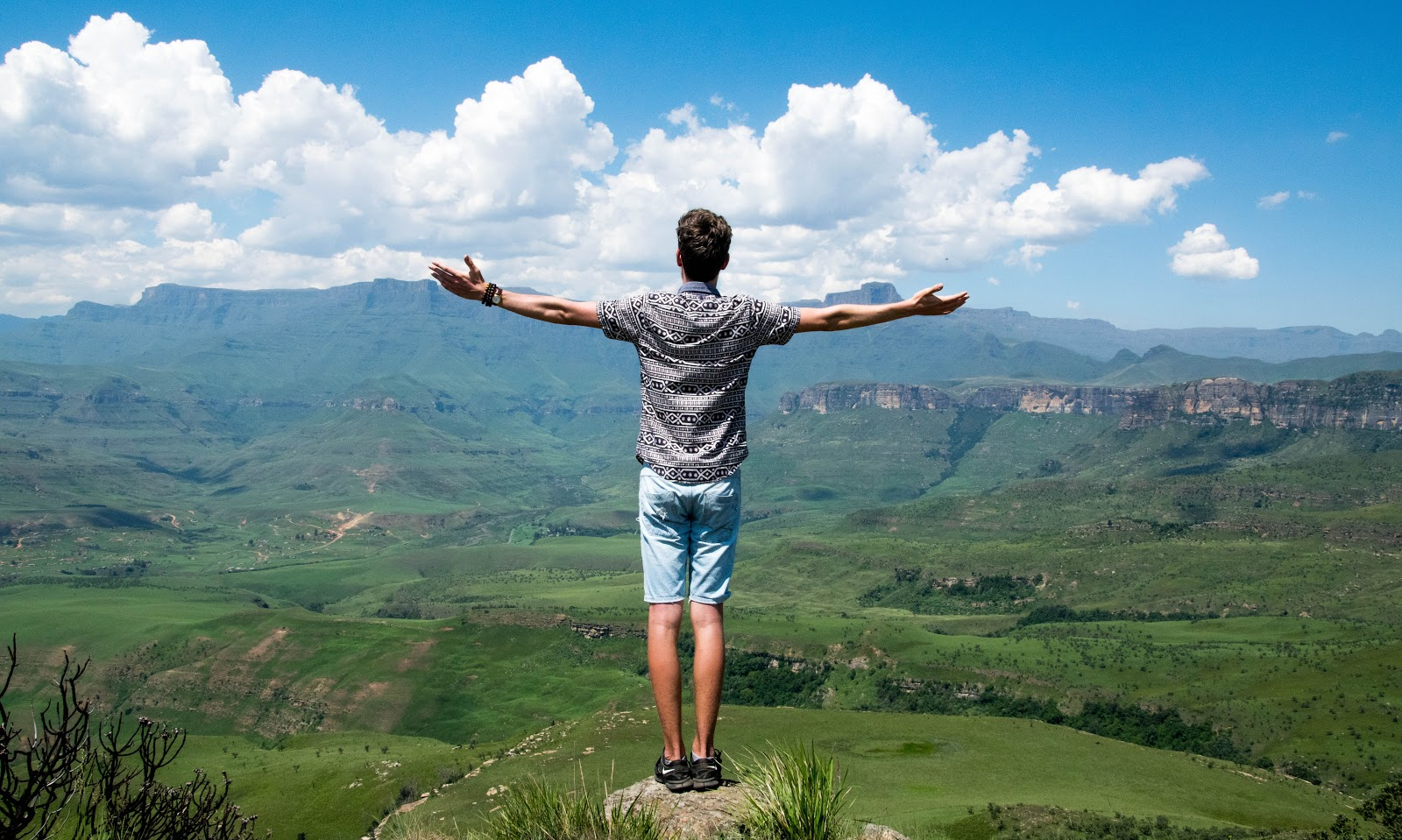 man standing on top of a mountain with open arms