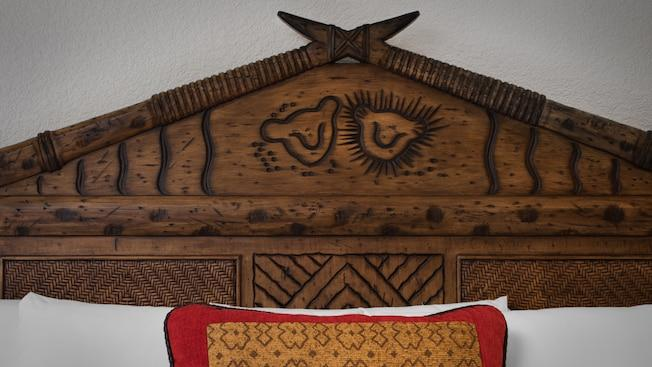 A bed with an African-themed frame and throw pillow