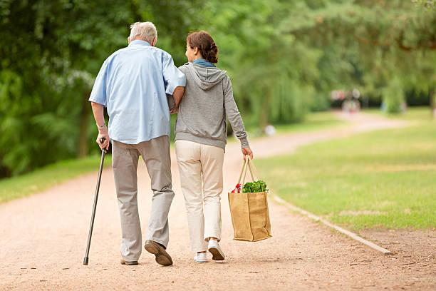 Caregiver – woman helping senior man with shopping Caregiver – woman helping senior man with shopping ageing parents stock pictures, royalty-free photos & images