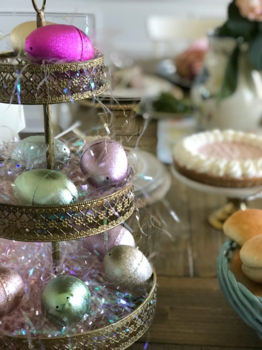 A three tier Easter decoration with colored eggs on it resting on an Easter table.