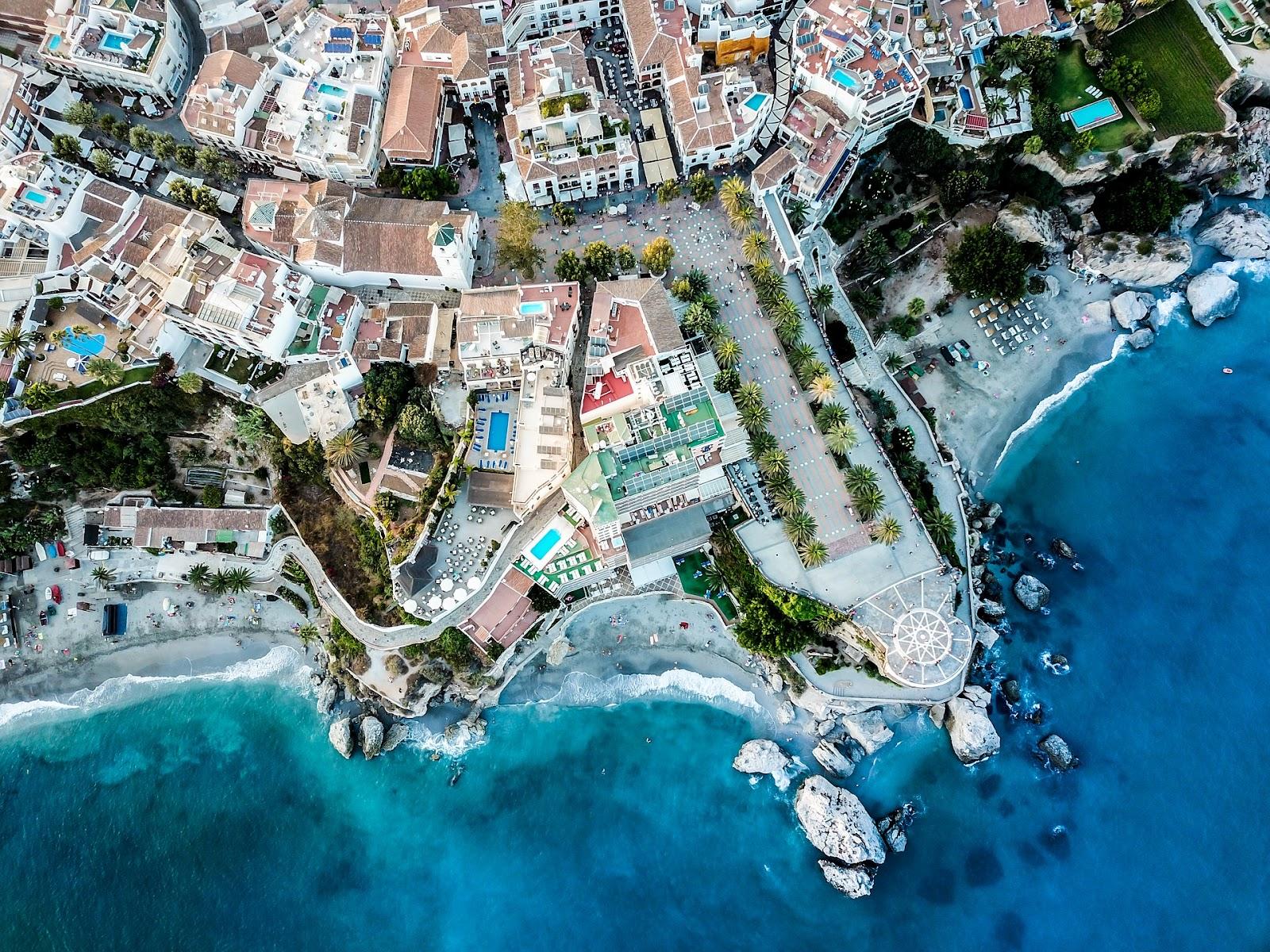 nerja beach aerial view blue sea water walking street palm trees buildings spain costa del sol