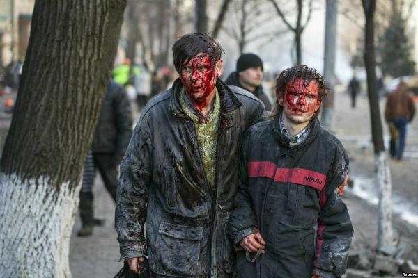 Одна из самых известных фотографий того драматического дня.  Киевские ученые отец и сын Николай и Игорь Кузнецовы были избиты боевиками «Беркута».  Фото Reuters