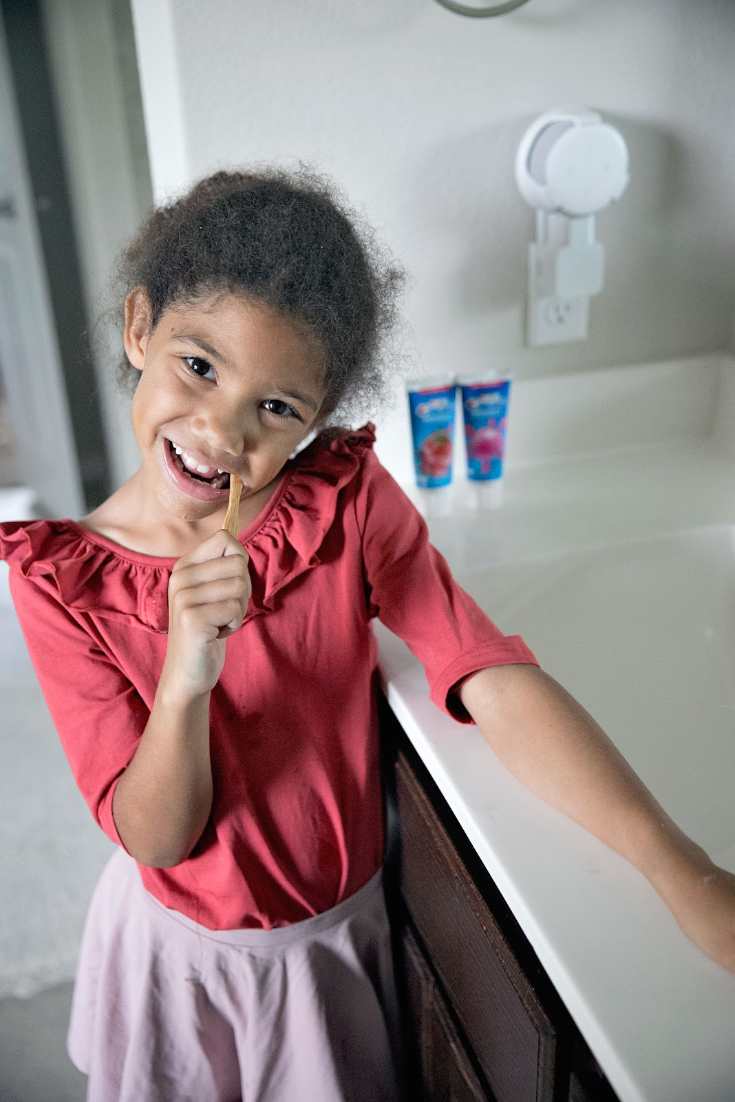 This is our mission to find the best kids toothpaste. Little girl brushing her teeth.
