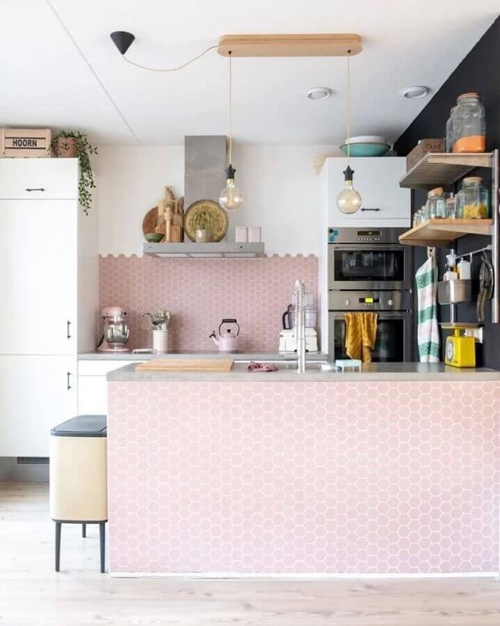 Cozinha com revestimento hexagonal em formato pequeno rosa  revestindo bancada e meia parede da cozinha, outra metade pintada de branco, armários brancos, parede lateral preta com prateleiras com temperos e piso amadeirado