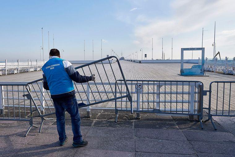 Рабочий устанавливает барьеры для посетителей причала на берегу Гданьского залива на время карантина из-за пандемии коронавируса, Сопот, Польша, 26 марта 2020 года