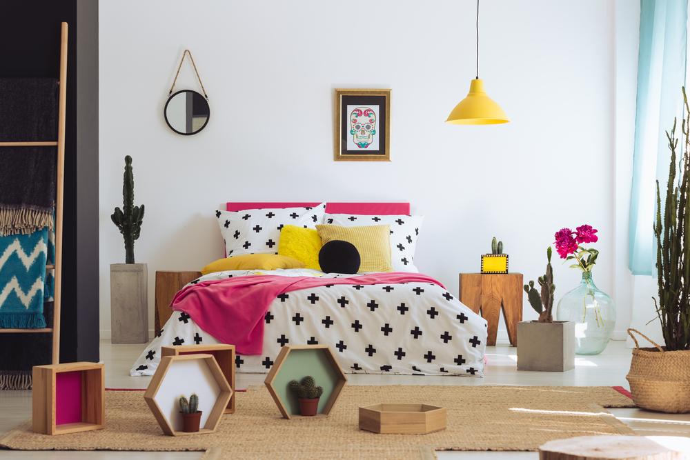 Um quarto contemporâneo com cores vibrantes e vários itens decorativos ao chão.