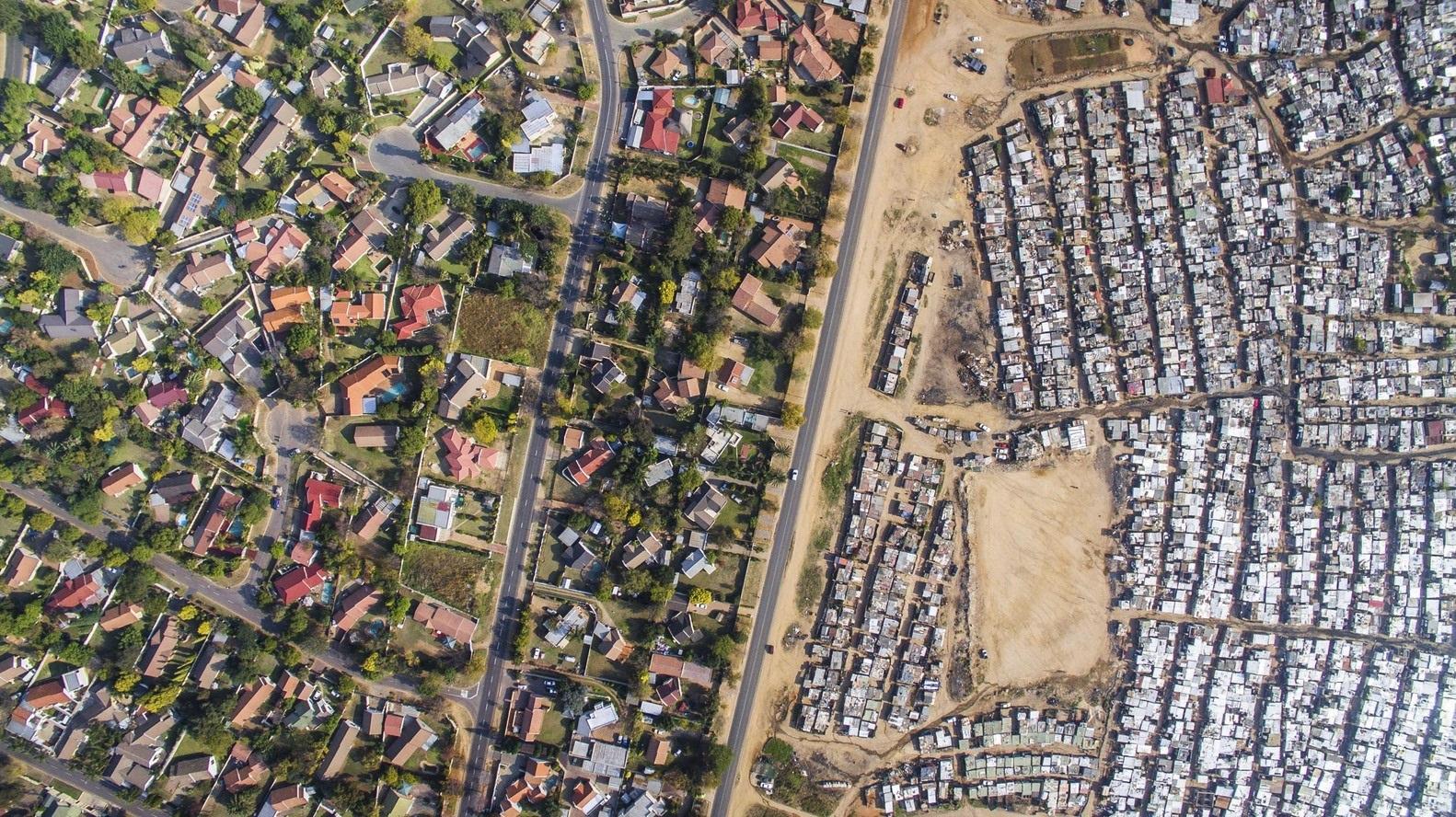 Do lado esquerdo, o bairro de Bloubosrand, à direita, o assentamento de Kya Sands. O território está localizado em Joanesburgo, na África do Sul, que leva o título de país mais desigual do mundo. (Unequal Scene/Reprodução)