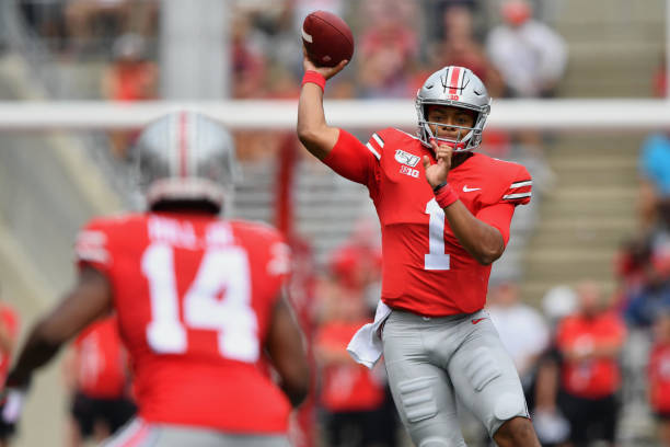 Quarterback Justin Fields of the Ohio State Buckeyes completes a pass to KJ Hill of the Ohio State Buckeyes for a first down in the third quarter...