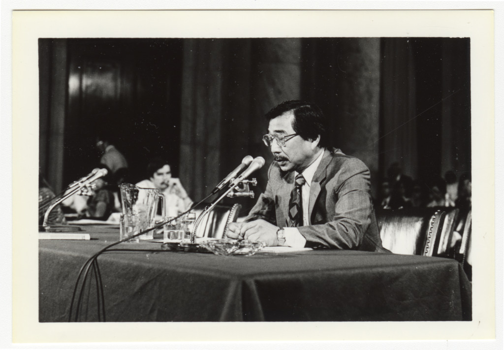 Gordon Hirabayashi seated at a table speaking into a microphone.