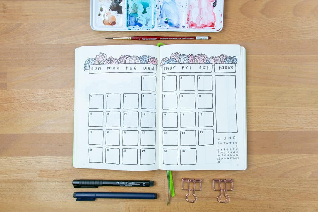 A flower themed calendar page open on table with materials strewn around it.