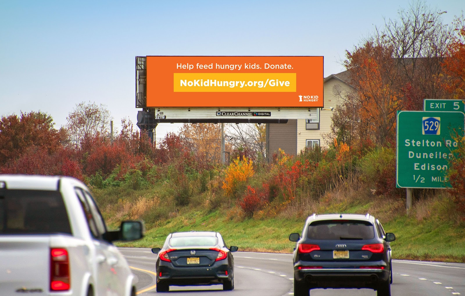 """A 'No Kid Hungry' billboard on a highway saying """"Help feed hungry kids. Donate. NoKidHungry.org/Give"""""""