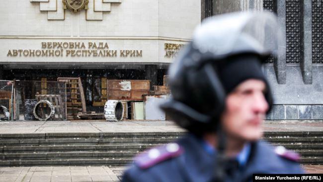 Сотрудник МВД Украины возле захваченного российскими военными здания Верховного Совета Крыма. Февраль 2014 года