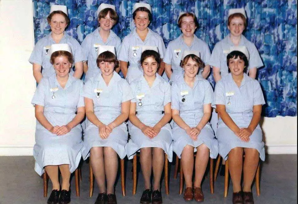Five nurses sitting on chair while other five are standing behind them