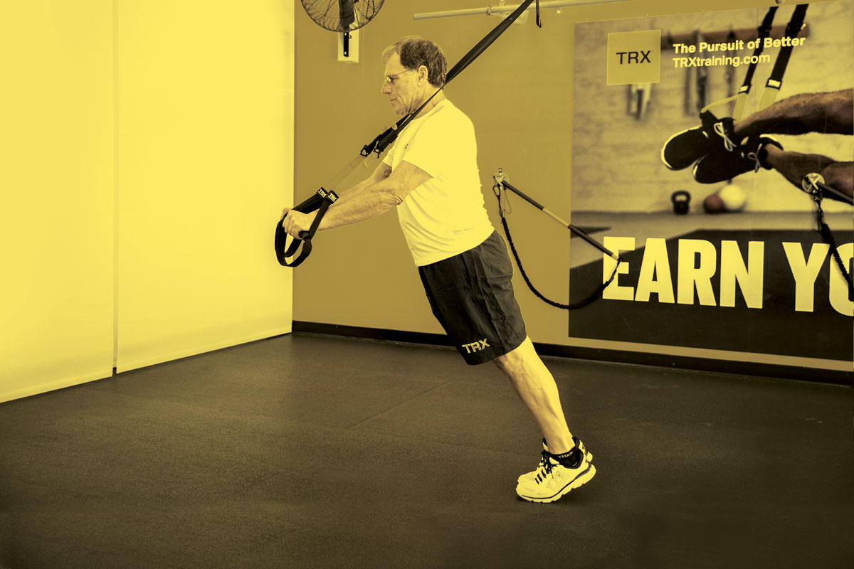 Man doing standing plank with TRX