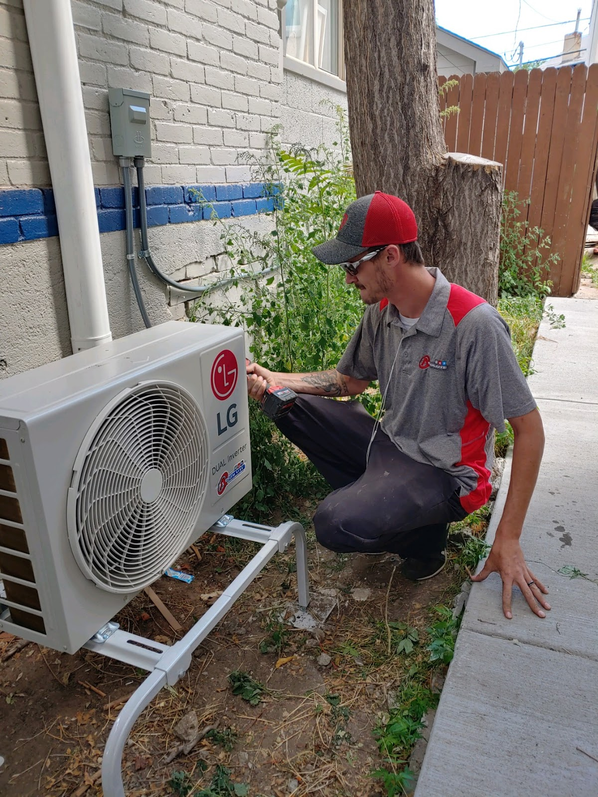 HVAC tech kneels to service an LG-branded mini-split air conditioner beside a brick home
