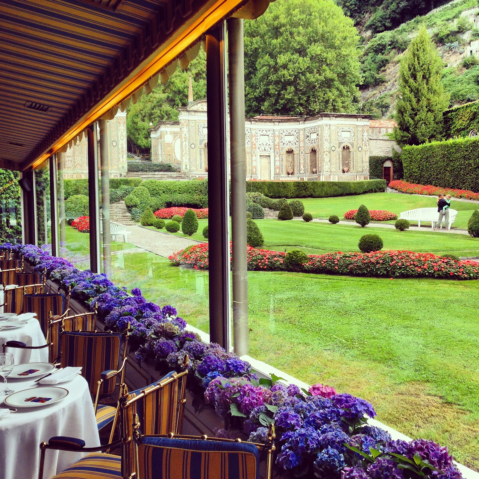 villa d'este restaurant. View the villa's beautiful garden while dining in the terrace. Empty, decorated tables, windows lined with purple flowers and park with tourist on bench.