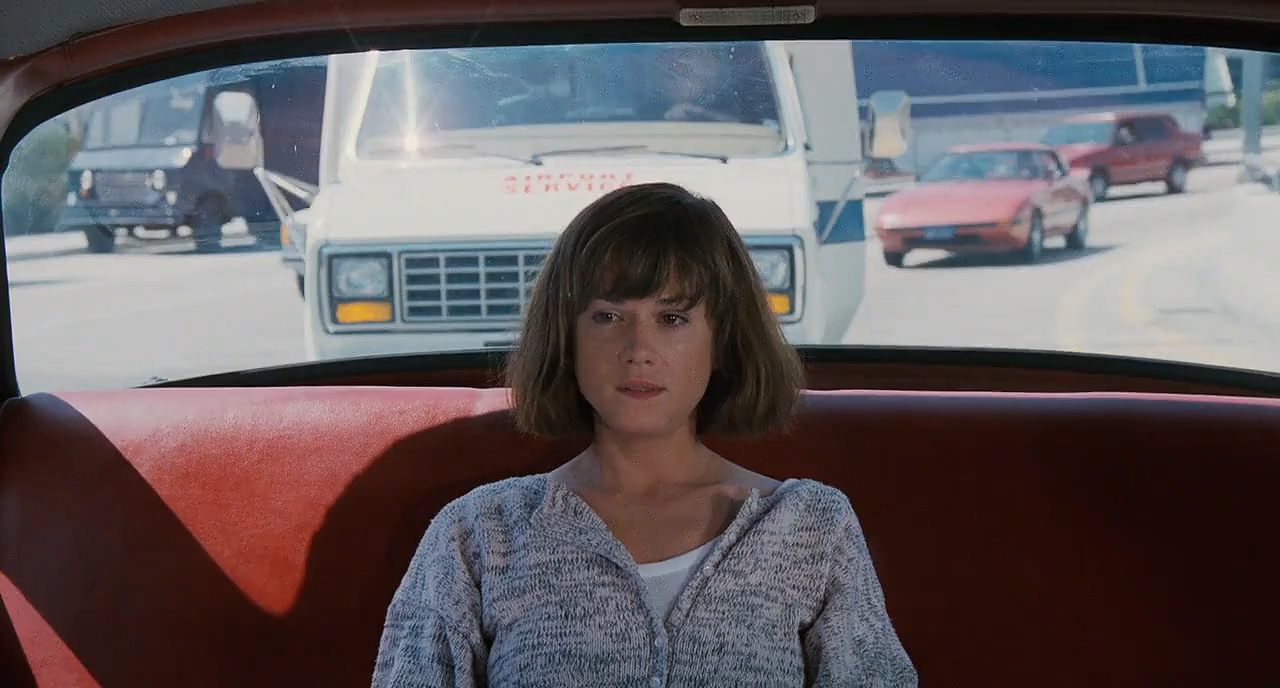 Holly Hunter as Jane Craig in Broadcast News. Jane, wearing a grey cardigan and white shirt, is sitting in the back of a car alone, looking pensive.