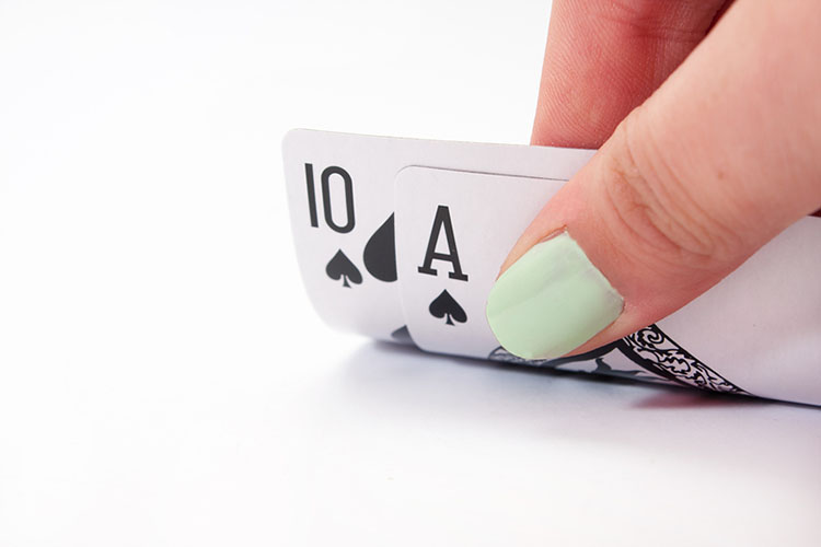 Woman with painted nails holds playing cards on white surface | The Dating Divas