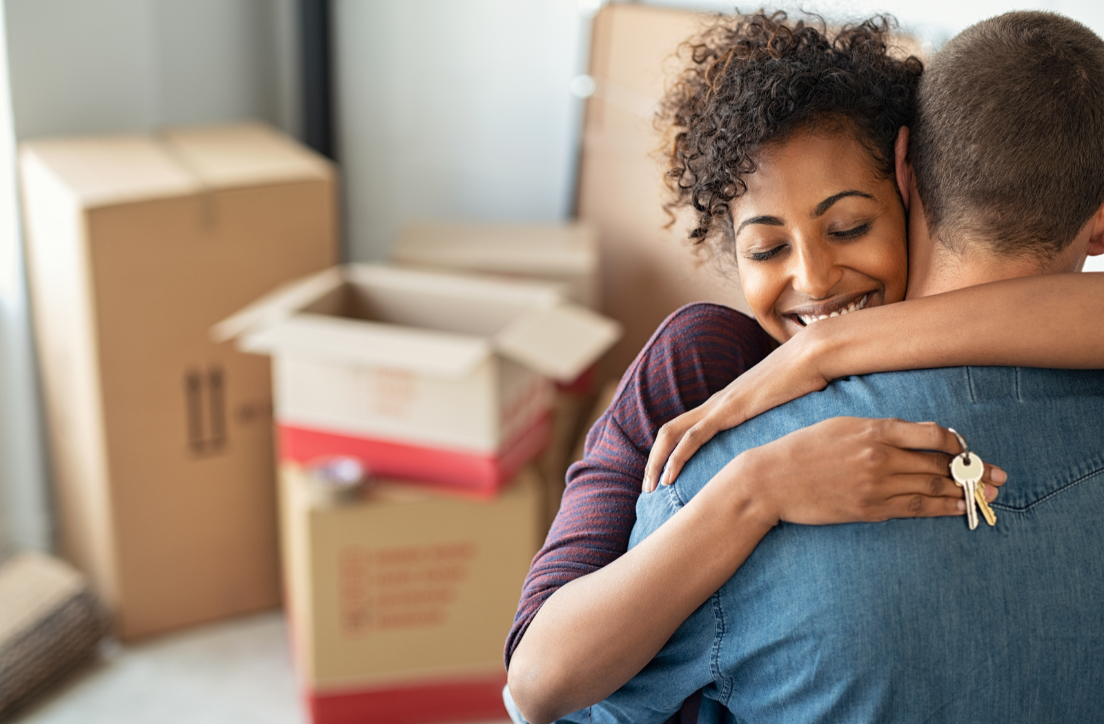 a woman hugging her partner holding keys to their new home with moving boxes in the back
