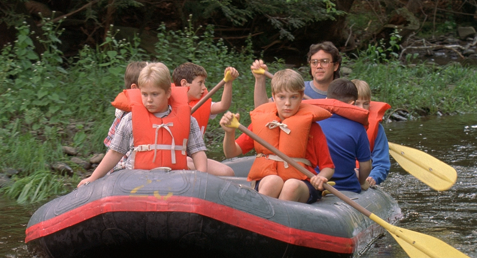 Neil (Lo Truglio) and his six young campers seen mid-rafting on a river with a green nature landscape behind them. This is right before they all decide that Neil should leave to find Victor, because otherwise they won't survive navigating through the river. Neil is sitting in the back. All children are seen wearing bright orange life jackets.