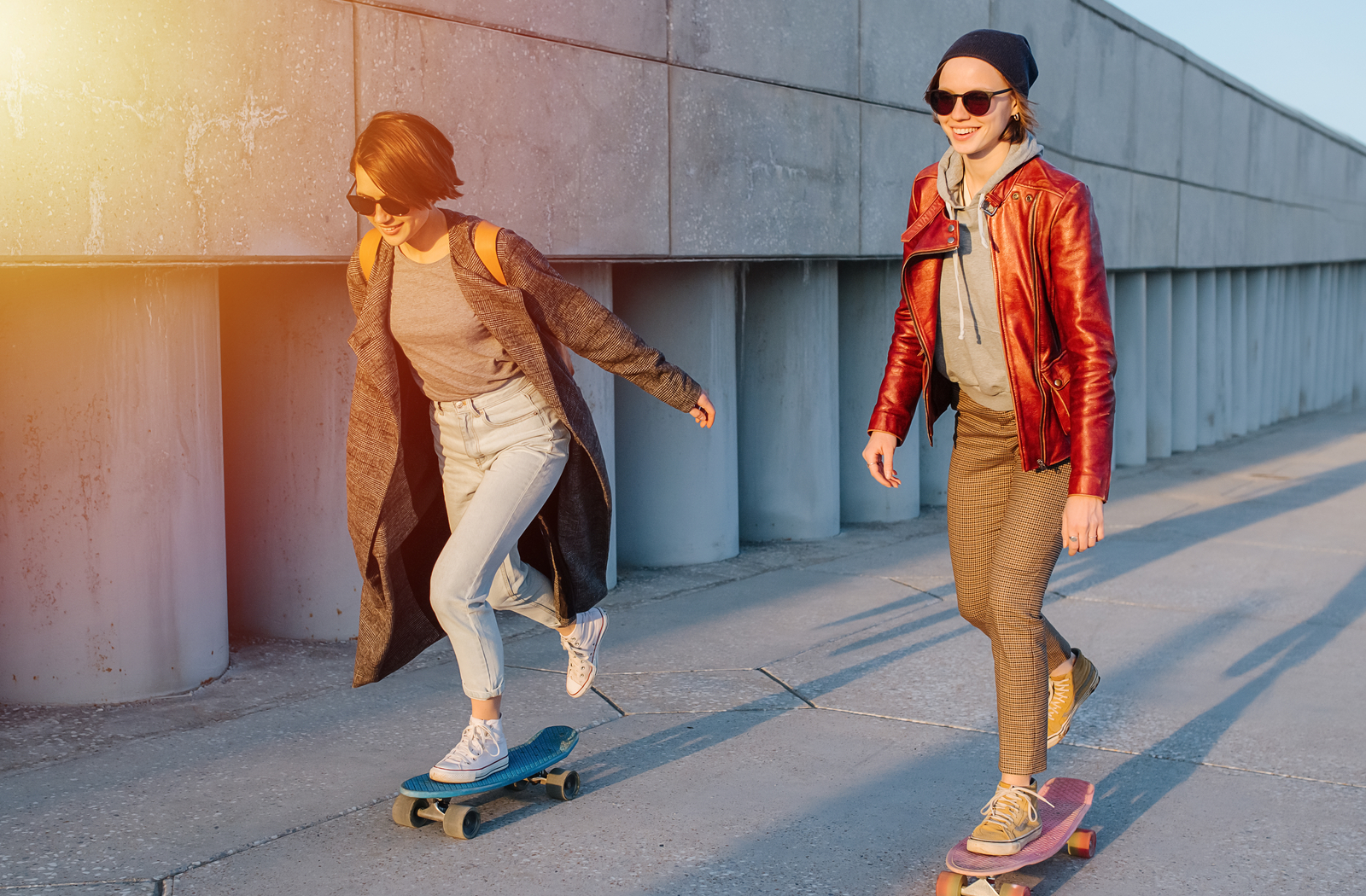 2 women longboarding by a concrete wall wearing sunglasses and smiling