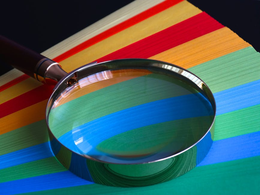 Magnifying glass on multicoloured card