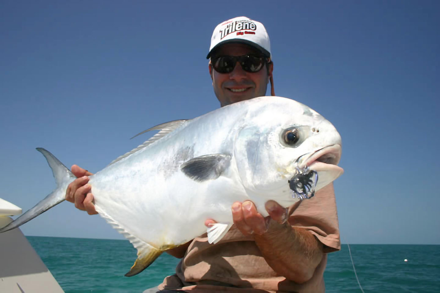 Image of angler holding a Permit caught on the fly in Key West