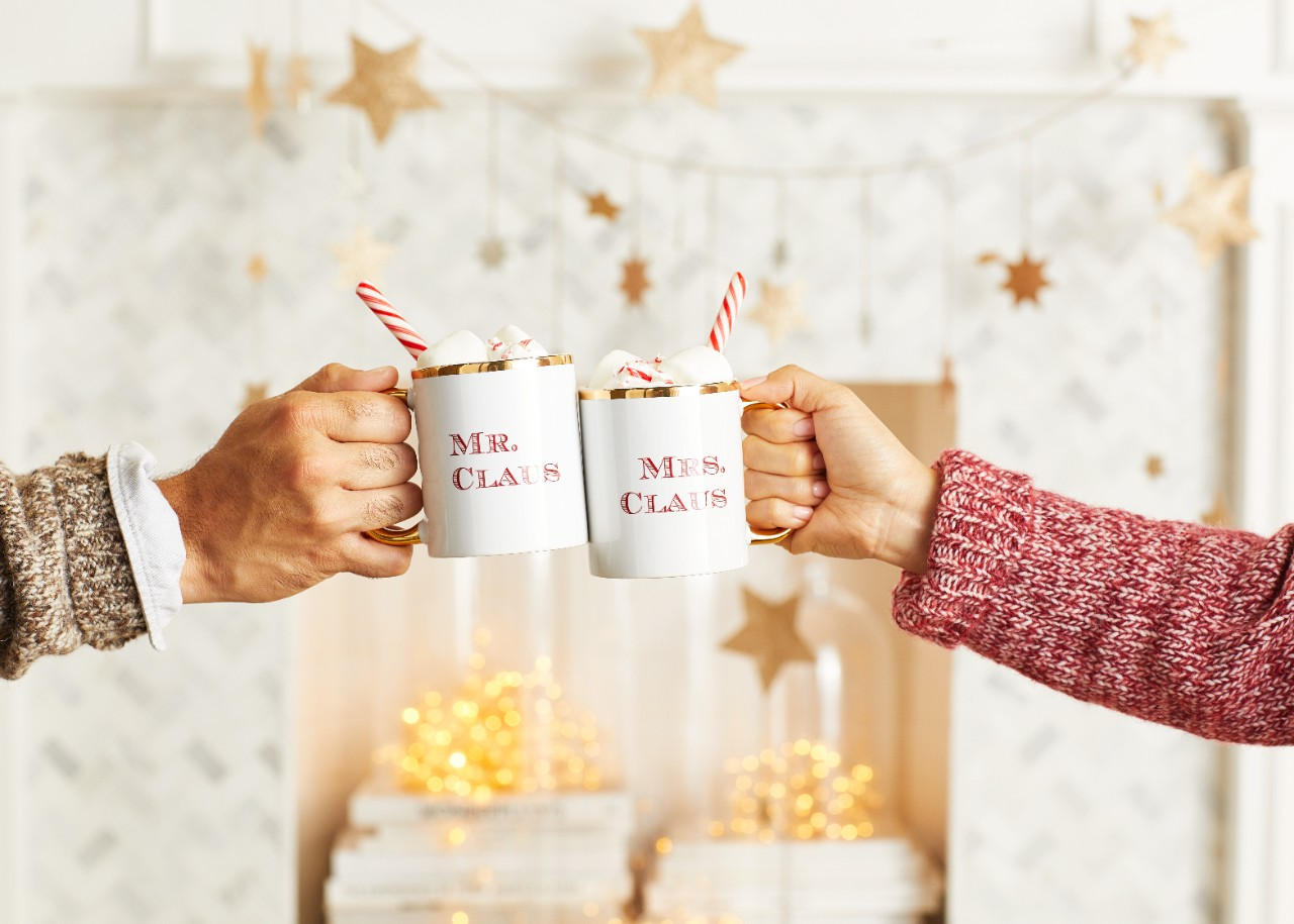 fun christmas card pose of mr. claus and mrs. claus hot chocolate mugs cheersing