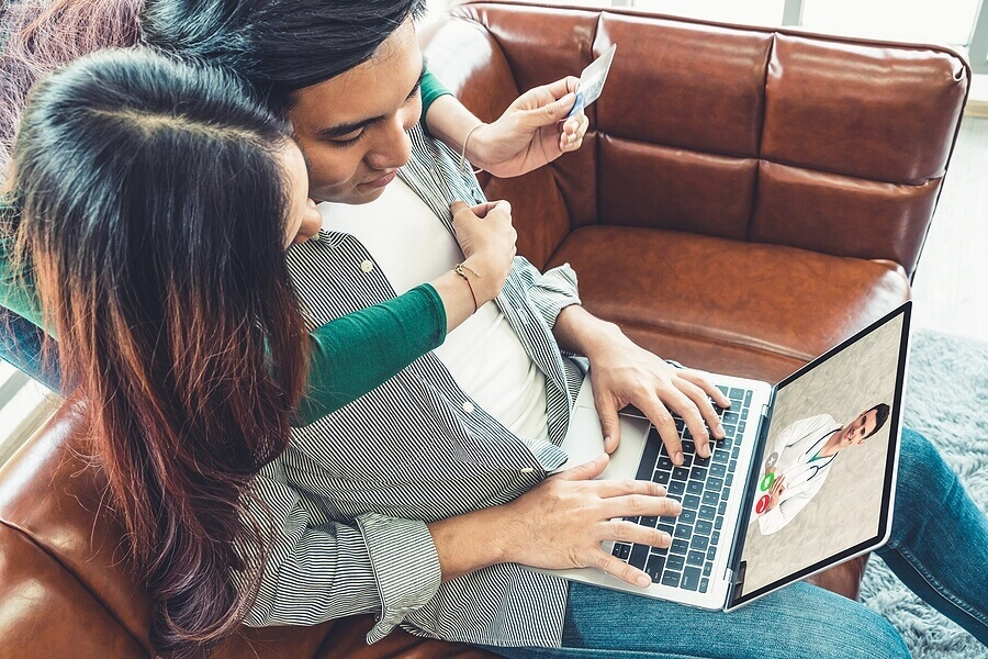 Ethnic couple receiving online therapy on couch. Man and woman hugging.