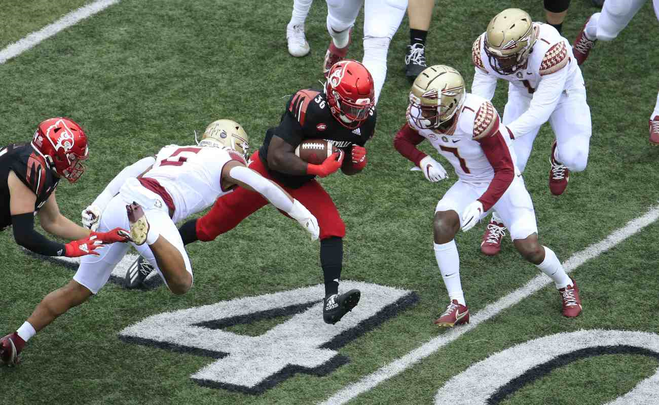 Three Florida State Seminoles players about to tackle Louisville Cardinals' Maurice Burkley.