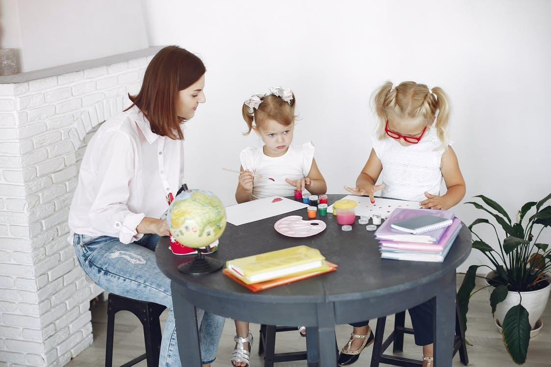 Two girls working on a sensory collage with their mother