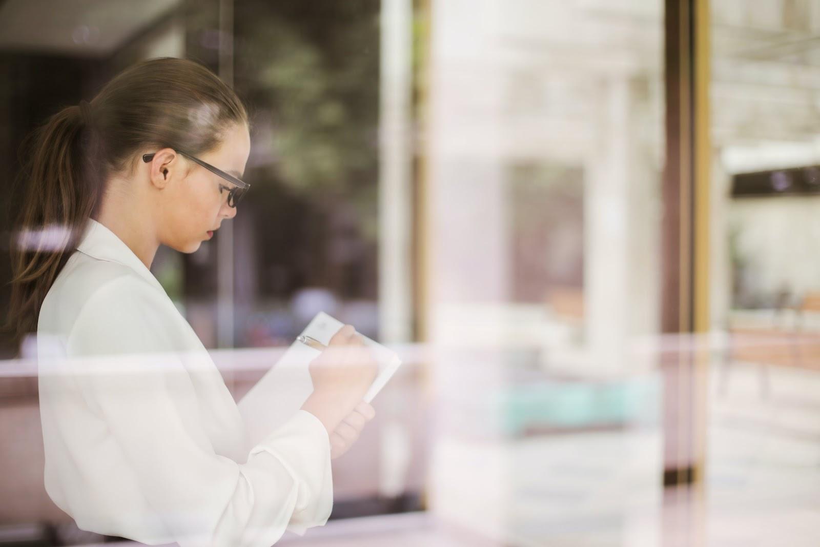 Uma mulher escrevendo algo em um papel.
