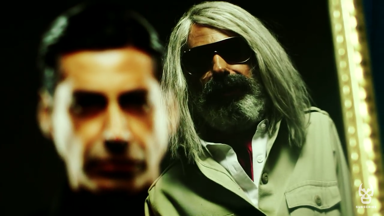 Image is of Antonio Cueto, a white haired bearded man wearing sun glasses and a white suit, standing in front of an out of focus image of his son, Dario Cueto, a younger man with slicked back dark hair and a surly expression.