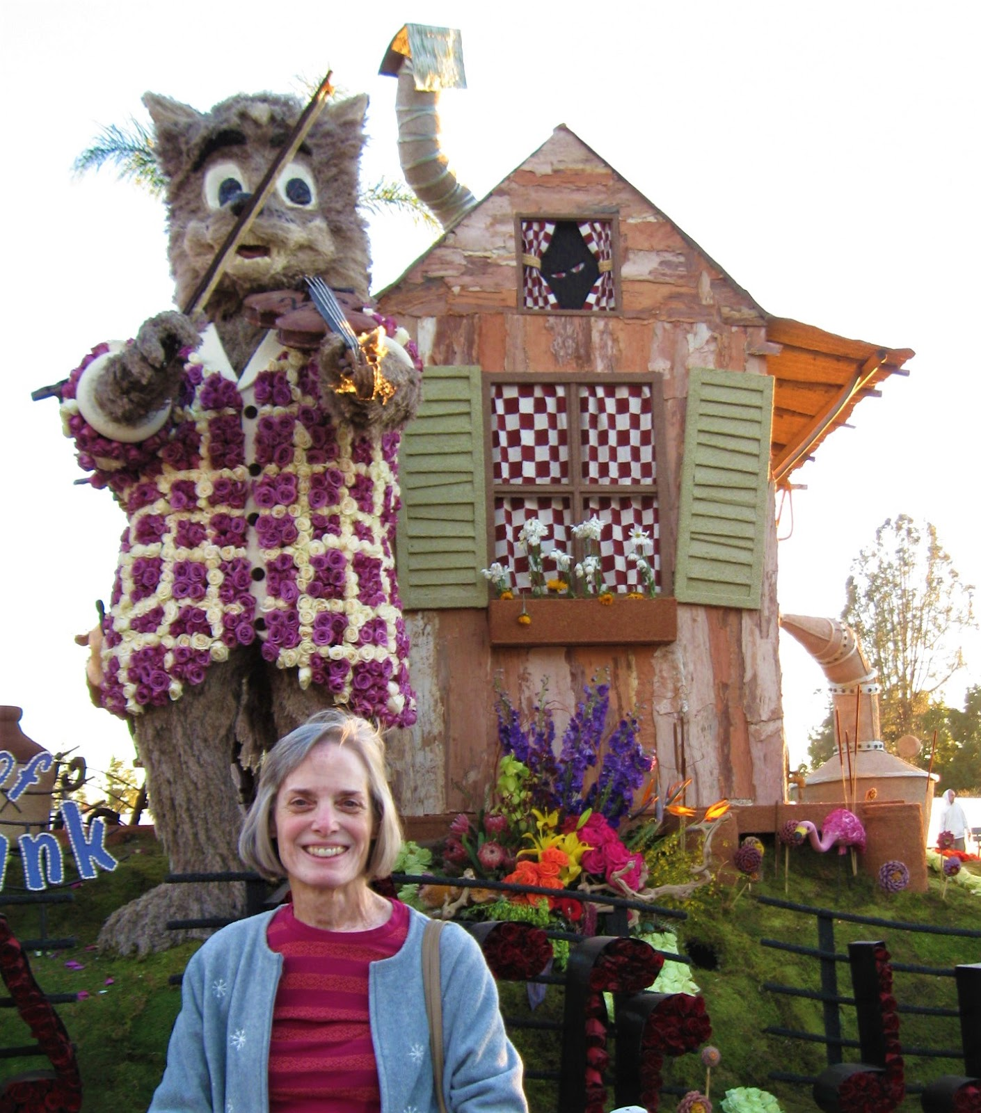 TOCTooler Beira Winter standing smiling in front of the Rose Bowl Parade float she helped with this year.  The float features a funky-looking house with crooked shutters, and a large cat in front playing the fiddle