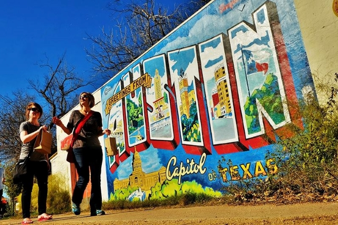 two women walking by a mural in an Austin neighborhood