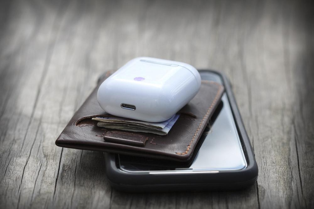 white wireless mini earphones and brown leather wallet on top of smartphone