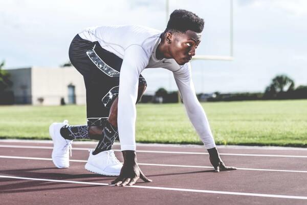 Foto de um homem negro se preparando para correr em uma pista de corrida profisisonal