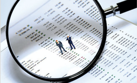 picture of magnifying glass fosuing on balance sheet with two small businessmen looking back