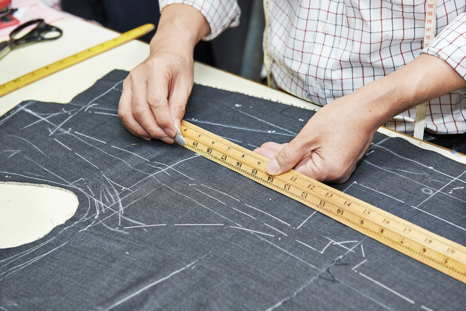 Singapore Tailor Guide_ tailor drafting with chalk and ruler