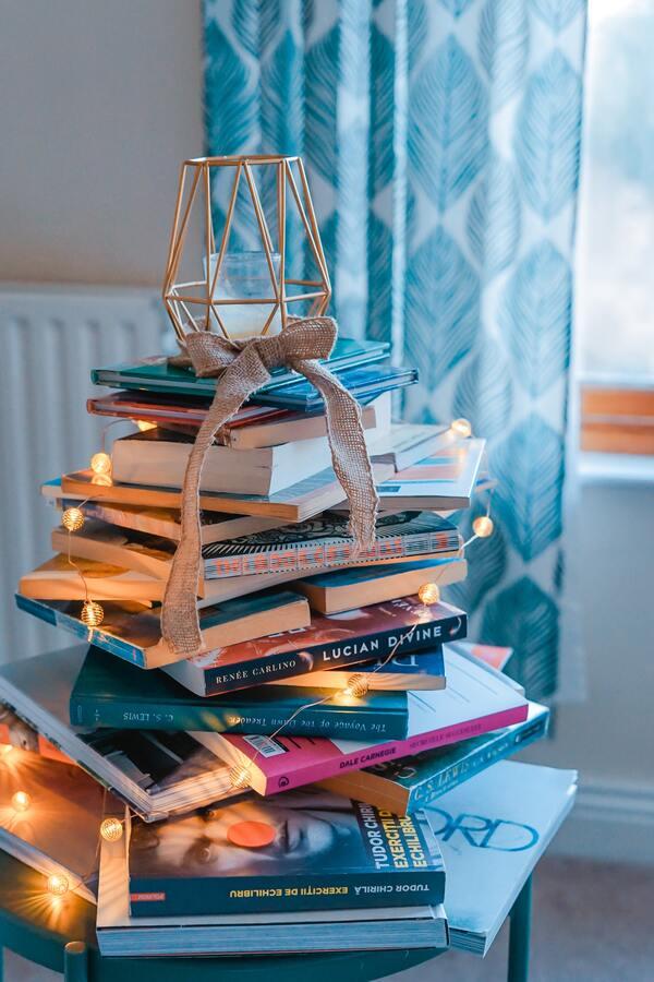 foto de vários livros empilhados com uma vela apagada em cima