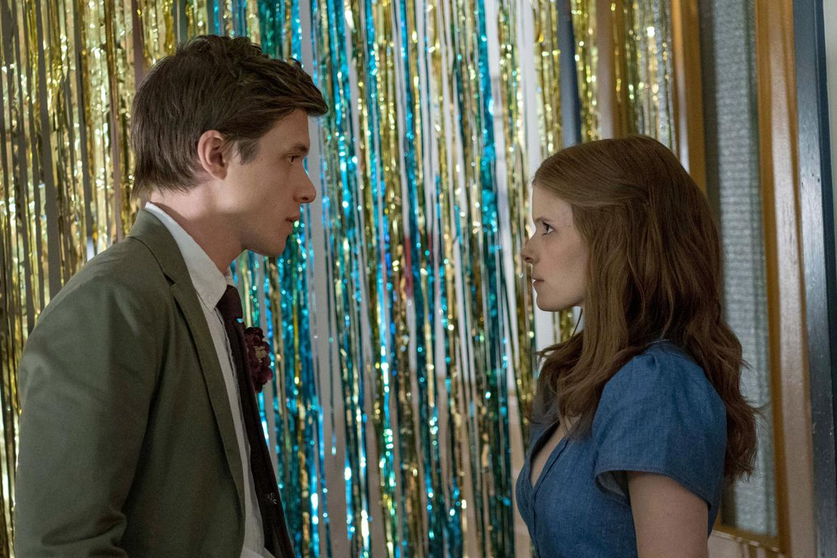 Nick Robinson and Kate Mara in A Teacher. Nick (left) and Claire (right) are standing facing each other in front of a backdrop of sparkly gold and blue streamers at a school dance. Nick wears a grey suit and tie, and Claire has a blue dress on.