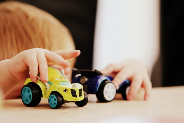 a kid playing with toy car